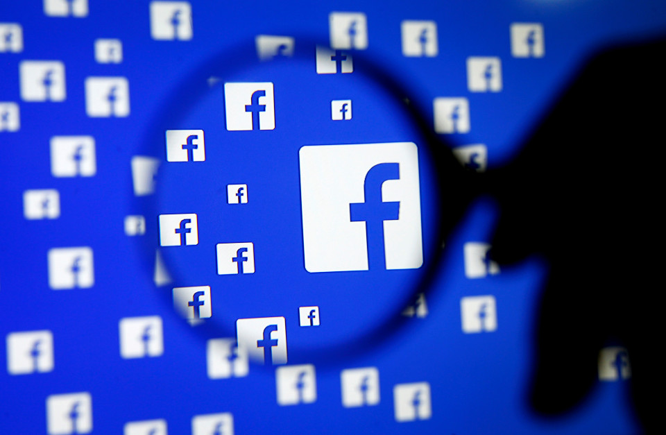 A man poses with a magnifier in front of a Facebook logo on display in this illustration taken in Sarajevo, Bosnia and Herzegovina, in this file photo from December 16, 2015. Facebook Inc smashed investors' expectations with a 52-percent jump in quarterly revenue as it sold more ads targeted at a fast-growing number of mobile users, sending its shares sharply higher after hours. REUTERS/Dado Ruvic/Files