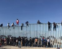 WATCH: Caravan Migrants Arrive at United States Southern Border, Scale Fence