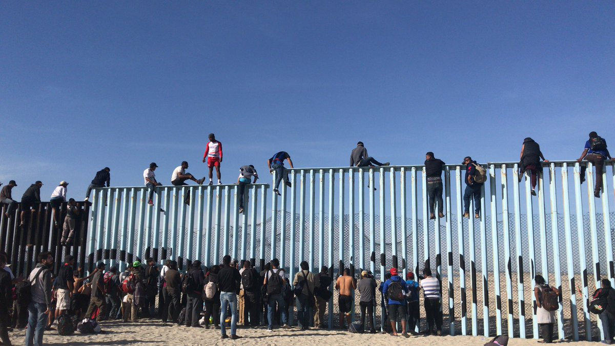 Caravan Migrants Arrive at United States Southern Border, Scale Fence
